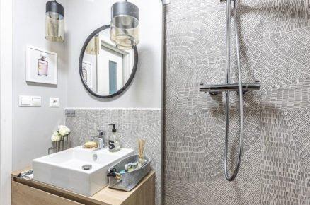 koupelna se vzorovaným obkladem, dřevěnou skříňkou s umyvadlem, sprchovým koutem, zrcadlem a závěsnými svítidlami