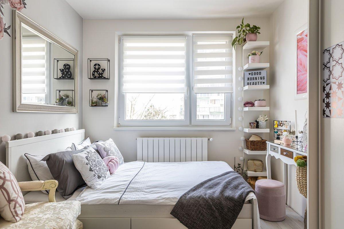 Ložnice v barvě šedé, bílé a růžové.