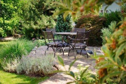 zahrada s andezitovou terasou se sezením, obklopena trvalkovými záhony