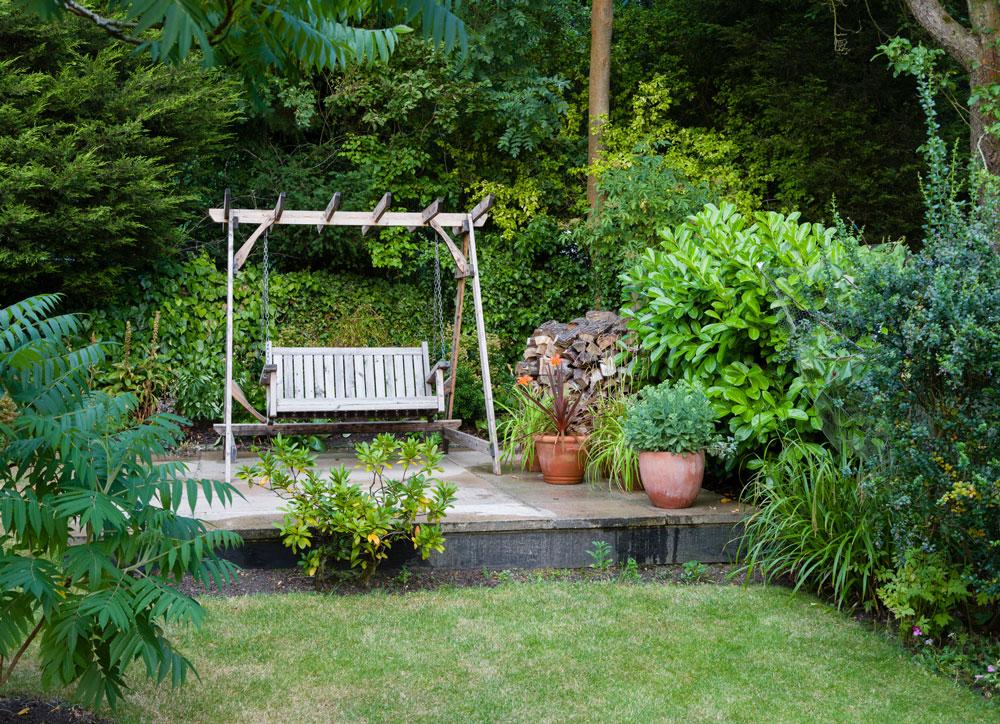 Jak vytvořit voňavou zahradu pro odpočinek: zahrada s houpačkou na betónové terase