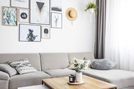 Obývací pokoj ve skandinávském stylu se šedou sedací soupravou a kovovými stoly
