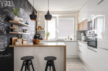 Kuchyně s bílou kuchyňskou linkou, ostrůvkem, barovými židlemi a černou tabulovou stěnou