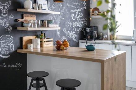 Kuchyně s černou stěnou a ostrůvkem s barovými židlemi