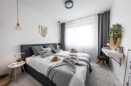Ložnice ve skandinávském stylu s čalouněnou postelí a odstínech šedé