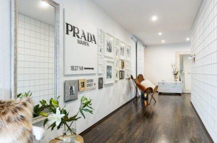 vstupná hala v rodinném domě s bílou stěnou z obkladů a rodinnými fotografiemi