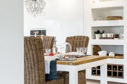 pohled do kuchyně ve venkovském stylu s bílou kuchyňskou sestavou zasazenou přímo do zdi