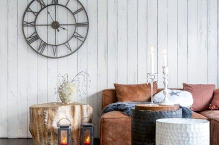 Obývací pokoj s tmavou podlahou, kožešinou, stolkem z kulatiny, hodinami a dřevěným bílým obkladem na zdi