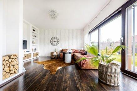 obývací pokoj s ručně malovaným bílým dřevěným obkladem, tmavou podlahou, výklenkem ve zdi sloužícím na odkládání dřeva a policemi s úložnými prostormi zasazenými přímo do zdi