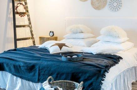 ložnice ve venkovském a skandinavském stylu s žebříkem se světelnou řetezí a dekoracemi na stěně nad postelí vyrobenými z prostírání