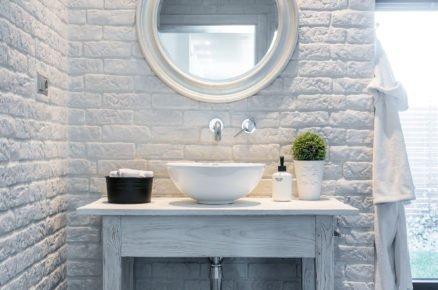 Detail koupelnové cihlové stěny se stolkem, umývadlem a zrcadlem
