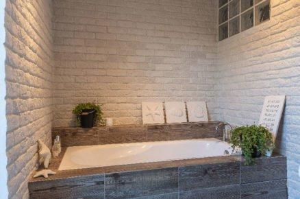 Koupelna s bílým cihlovým obkladem a vanou