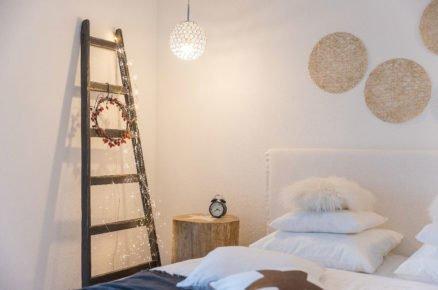 Detail ložnice s žebříkem se světelnou řetezí, stolkem z kulatiny a budíkem