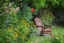 okrasná zahrada s trvalkovými záhony a dřevěnou židlí