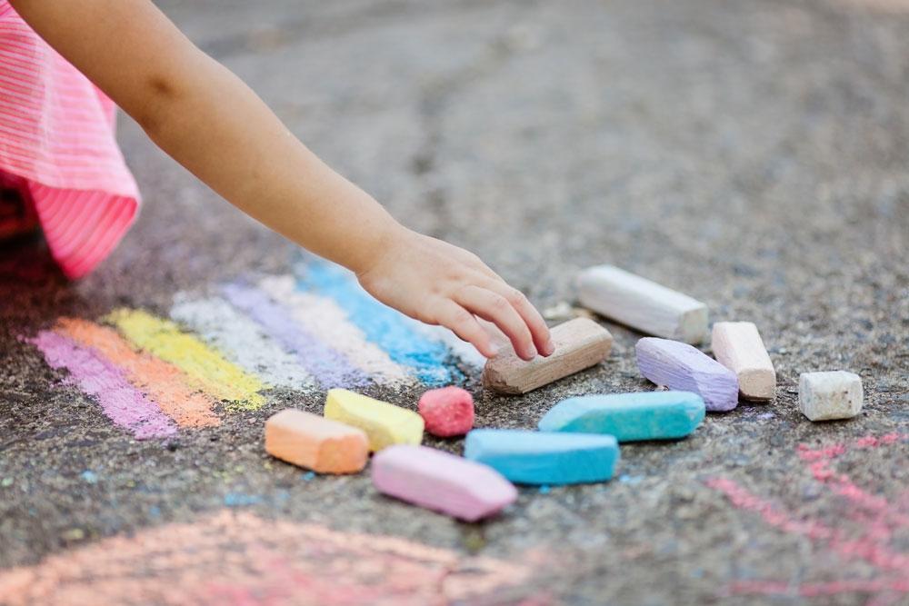 díte kreslí s barevnými křídami