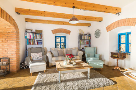 obývací pokoj ve venkovském stylu s dřevěnými trámi na zdi a nadokenními oblouky z cihel