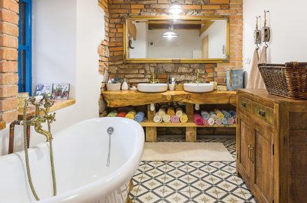 koupelna ve venkovském stylu s vanou na zlatých nožičkách, přiznanou cihlovou zdí a umývadly položenými na masivním kusu opracovaného dřeva