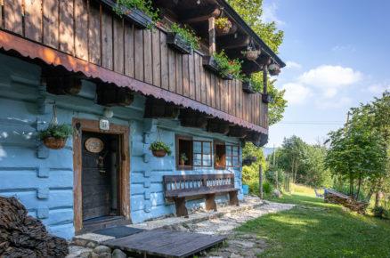modrá tradiční chalupa s dřevěnou verandou