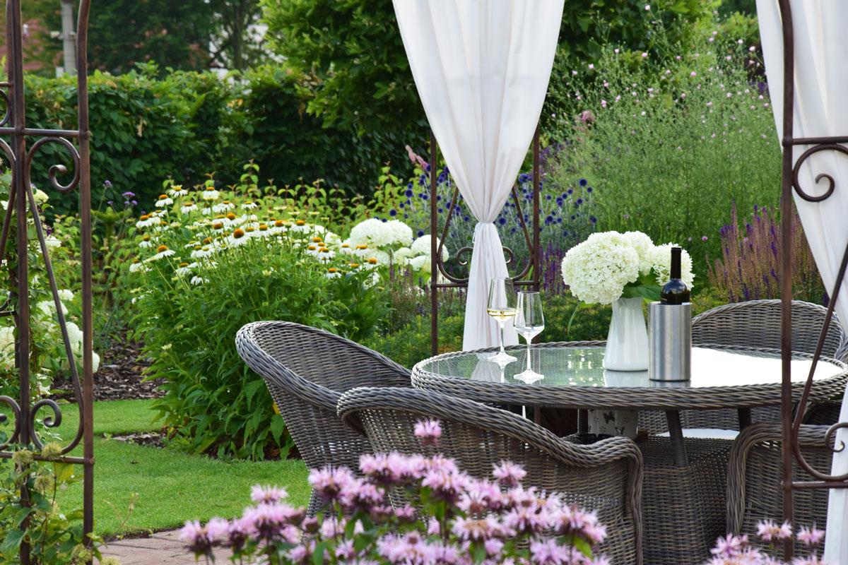 okrasná zahrada s altánkem a ratanovým sezením