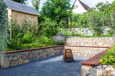 svahovitá zahrada s kamennými zídkami z pískovce a přenosným ohništěm