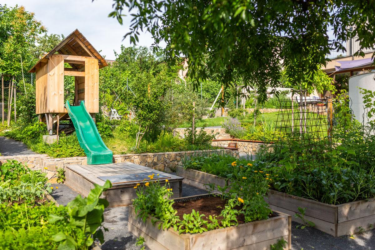 zahrada ve svahu s vyvýšenými záhony a domkem pro děti kterého klouzačka vede do pískoviště