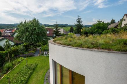rodinný dům se zelenou střechou a zahradou ve svahu