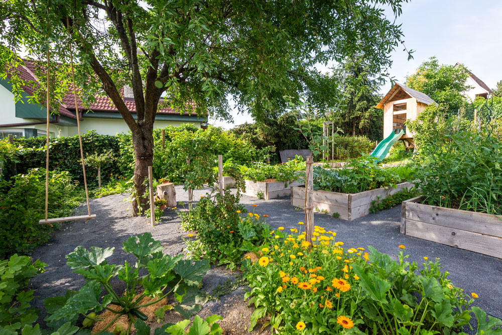zahrada vybudovaná ve svahu, bez trávníku, s vyvýšenými záhony se zeleninou a bylinkami, domkem pro děti a houpačkou na stromě